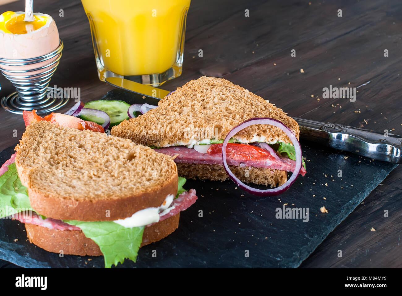 Sandwich fait maison avec du bacon, tomate, laitue, verre de jus de fruits,  café, oeuf, sur le petit-déjeuner sur le tableau noir. Copier l espace. d238be058734