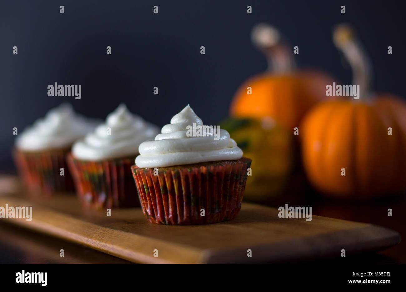 Delicious Pumpkin Spice Cupcakes avec glaçage au fromage à la crème avec des citrouilles en arrière Photo Stock