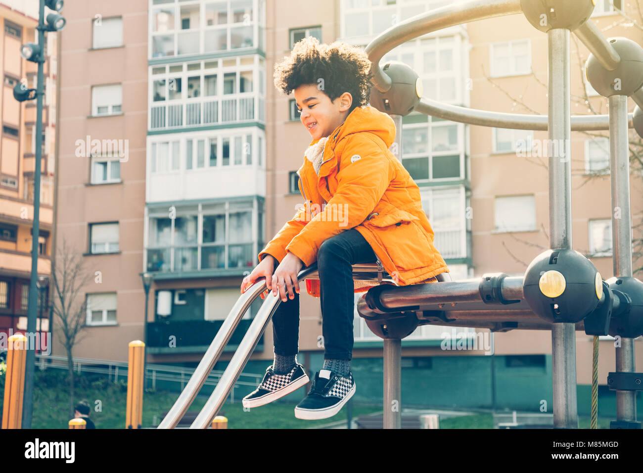 Happy kid en manteau orange escalade sur l'aire de jeux dans une journée ensoleillée Photo Stock