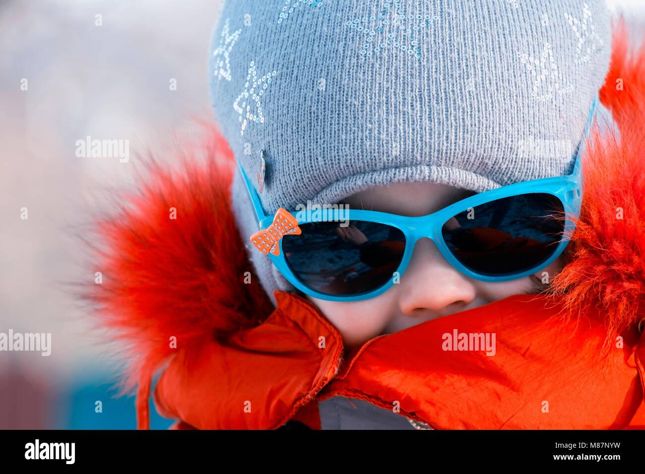 Portrait d'une petite fille à lunettes de soleil en hiver Photo Stock