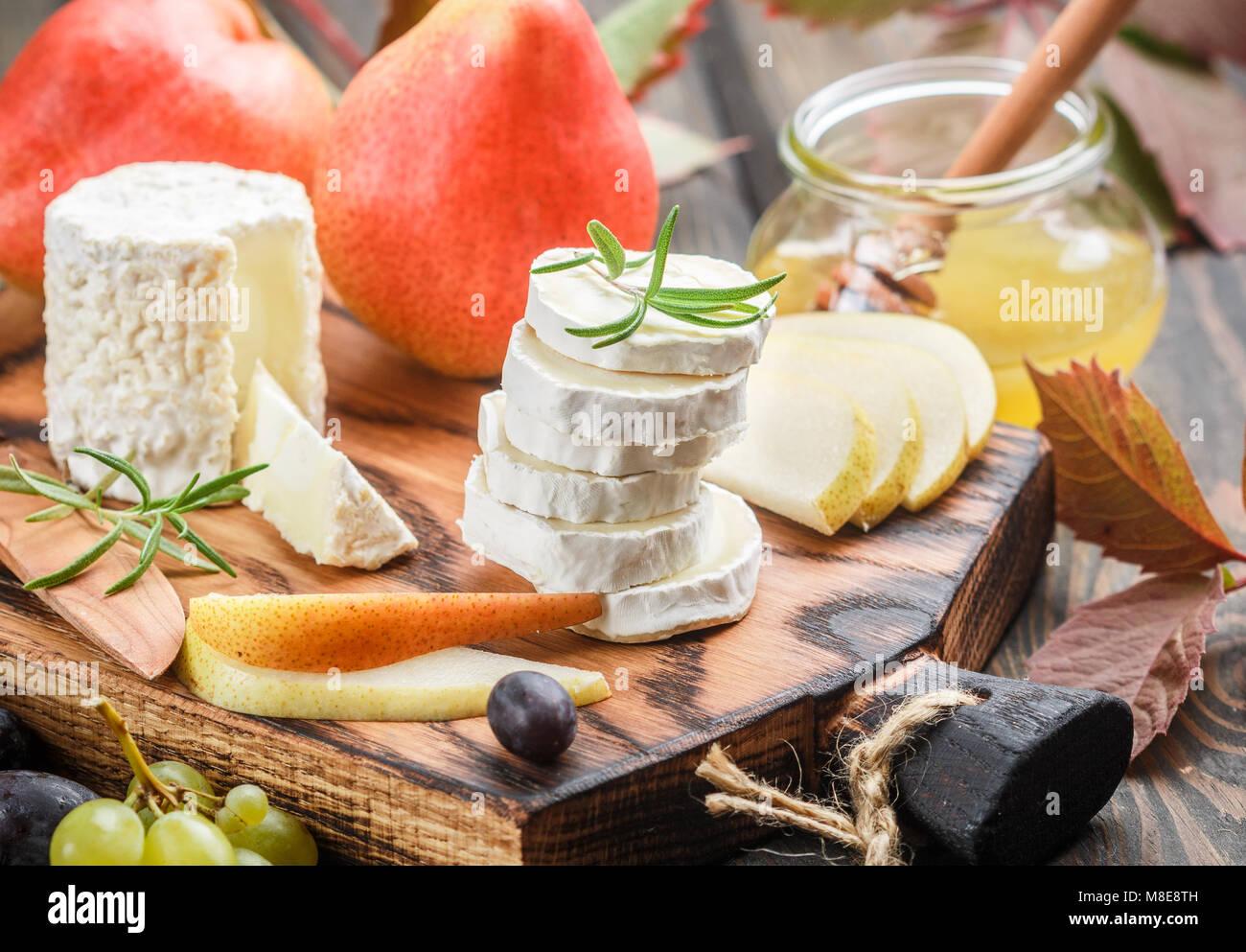 Le fromage de chèvre avec des fruits et du miel. Le Camembert. Bree. Le raisin, la poire et le romarin. Vin Photo Stock