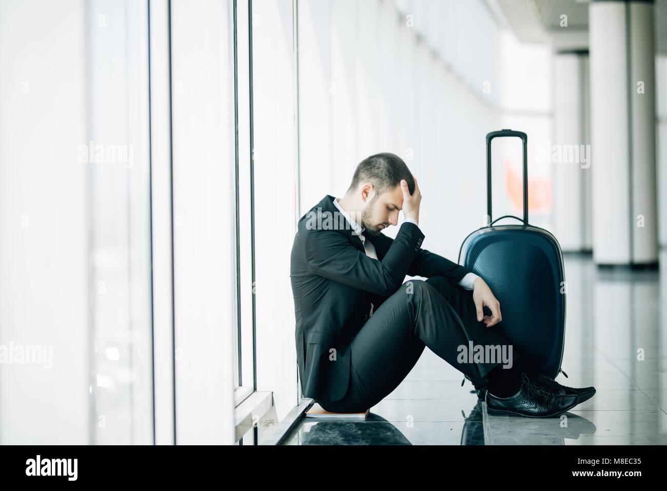 Business man sitting at the airport terminal sur le plancher avec valise vol retardé, deux mains se touchent en tête, maux de tête, attendant le voyage. Banque D'Images