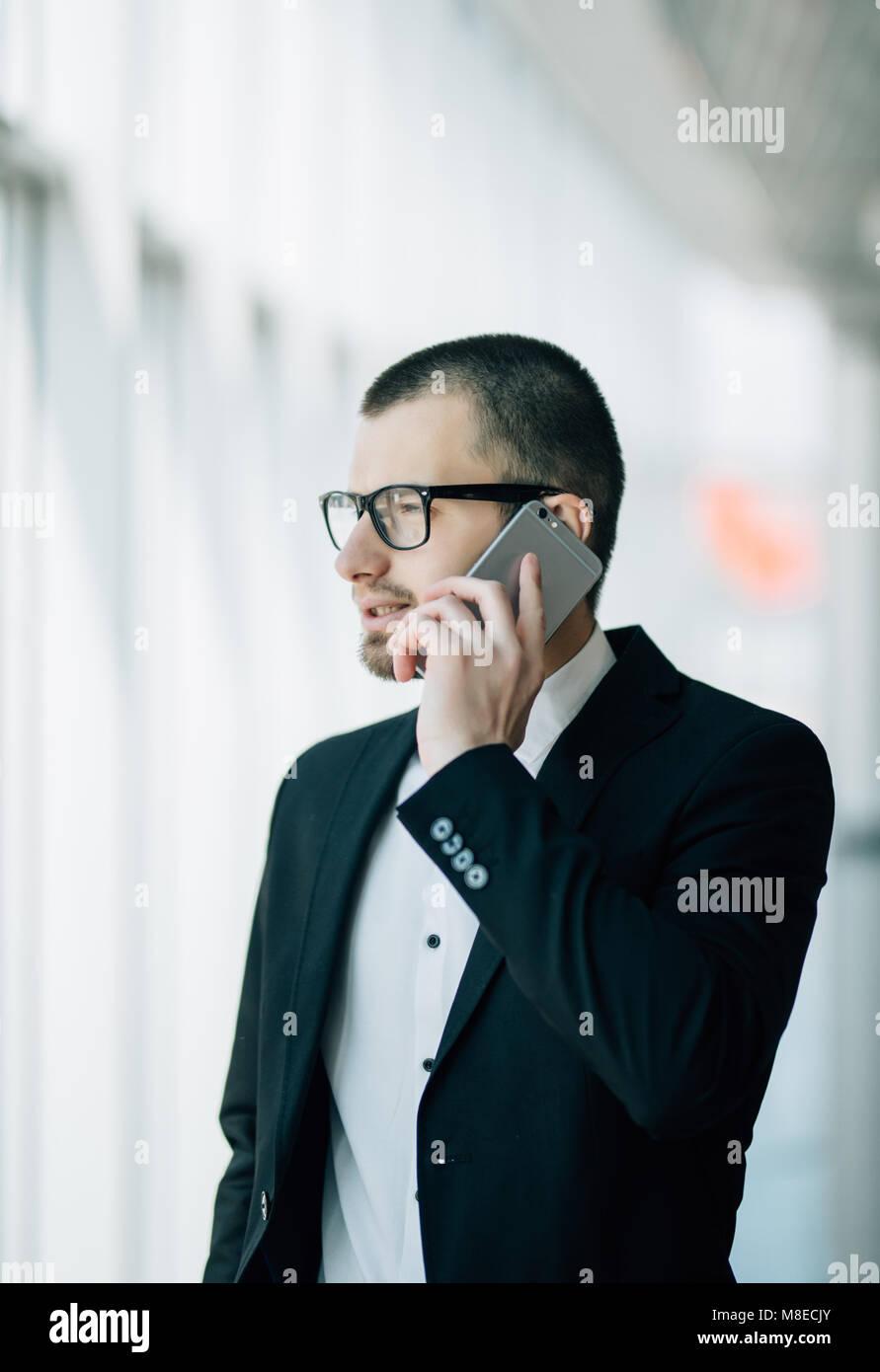 L'homme d'affaires à maturité à l'intérieur du bâtiment de bureaux et l'utilisation de téléphone cellulaire. Homme Banque D'Images