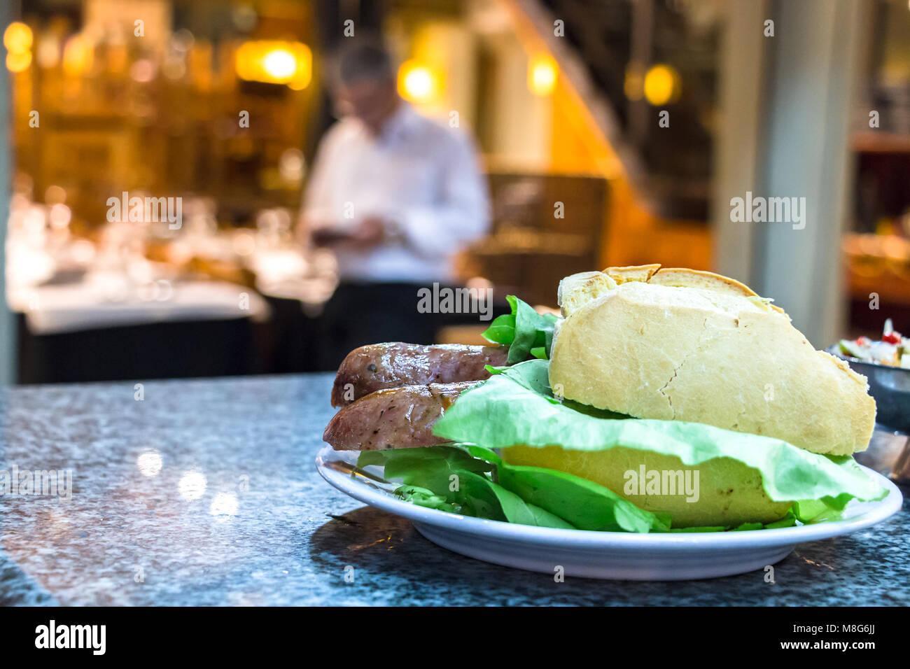 Un choripan sandwich avec salade et pain blanc français sur un comptoir à Mercado del Puerto, Montevideo, Photo Stock