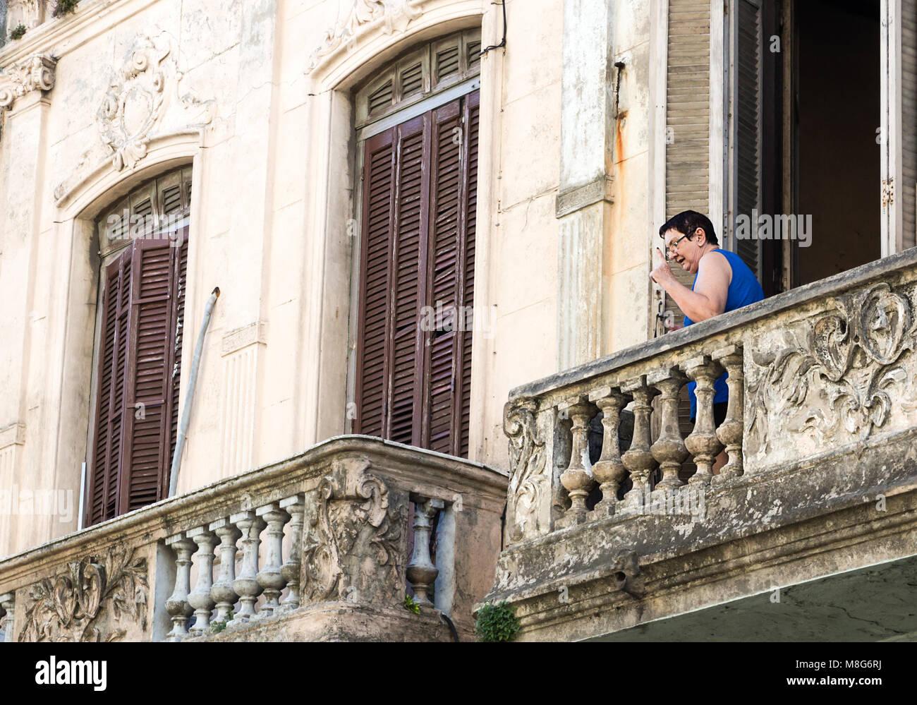 Montevideo, Uruguay - 25 Février 2018: A senior woman pointant vers le haut depuis le balcon de son domicile Photo Stock