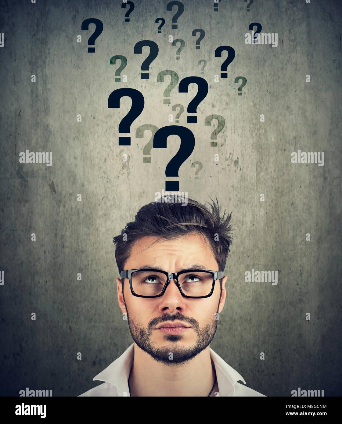 Homme perplexe avec trop de questions et pas de réponse Banque D'Images