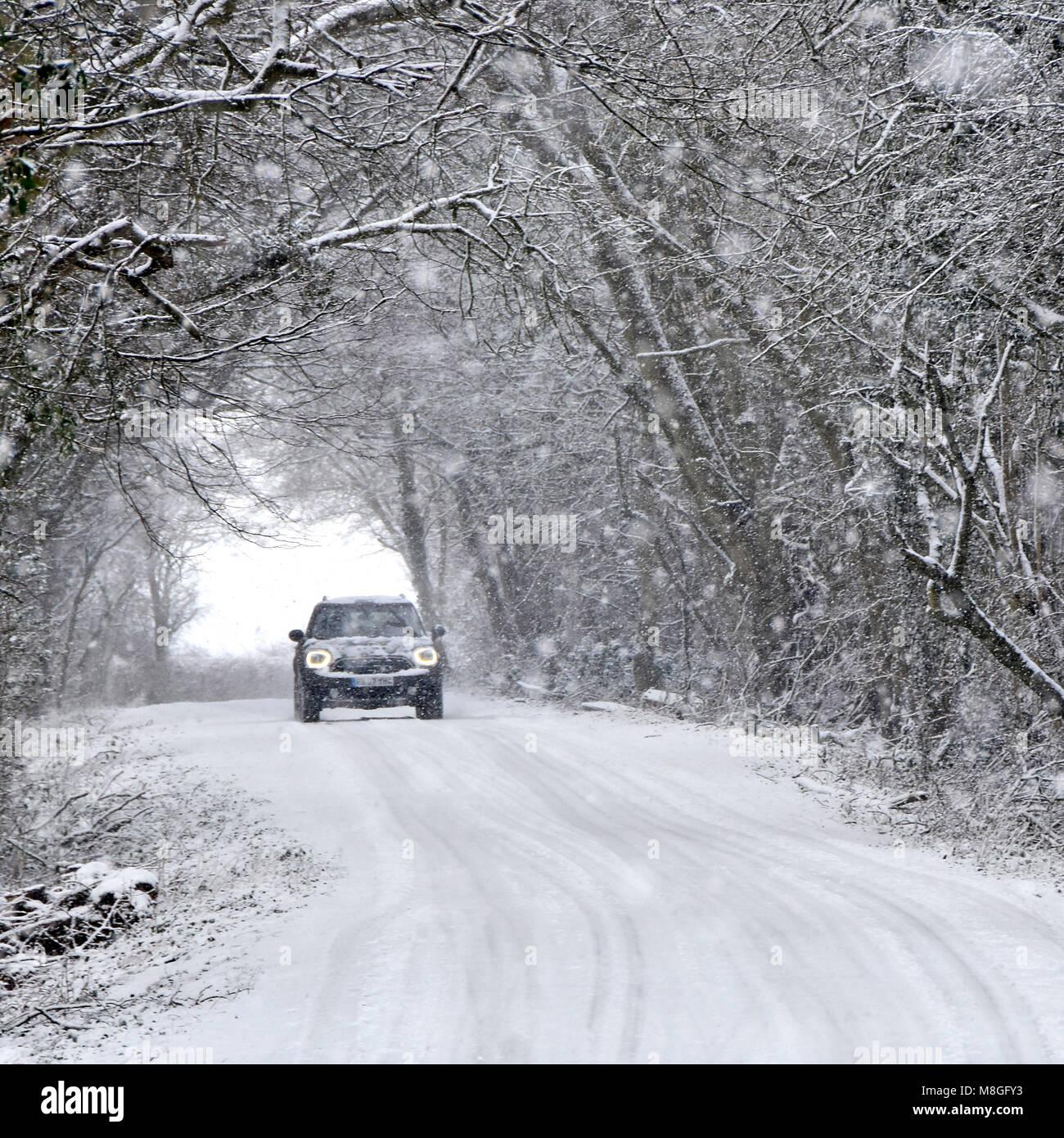 Les phares de voitures sur la conduite dans la neige qui tombe on country road tunnel arbre couvert de neige neige scène forestiers mauvais hiver météo England UK Banque D'Images