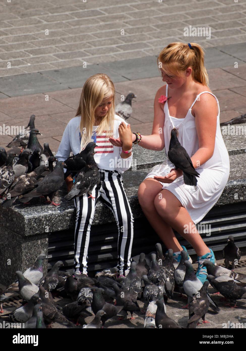 Deux adolescentes se nourrir les pigeons sur la place principale, à Cracovie. Photo Stock