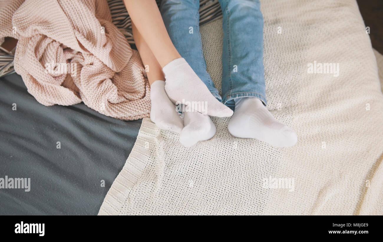 Les jambes du jeune beau couple cuddling et se réveiller ensemble, les relations familiales Photo Stock