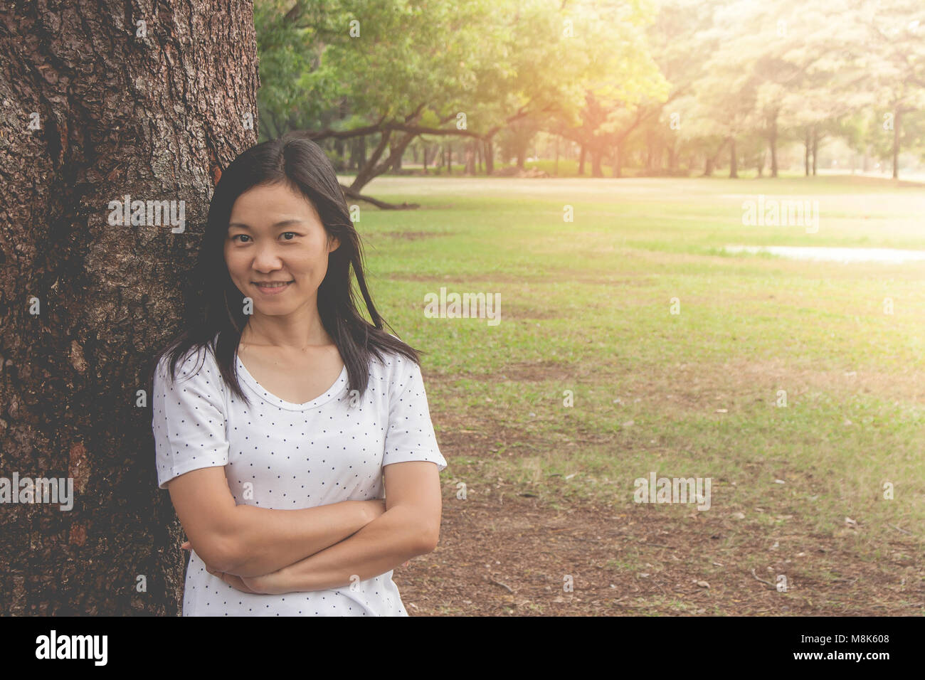 Maison de vacances et de Concept : Woman wearing white t-shirt. Elle debout sur l'herbe verte et le sentiment Photo Stock