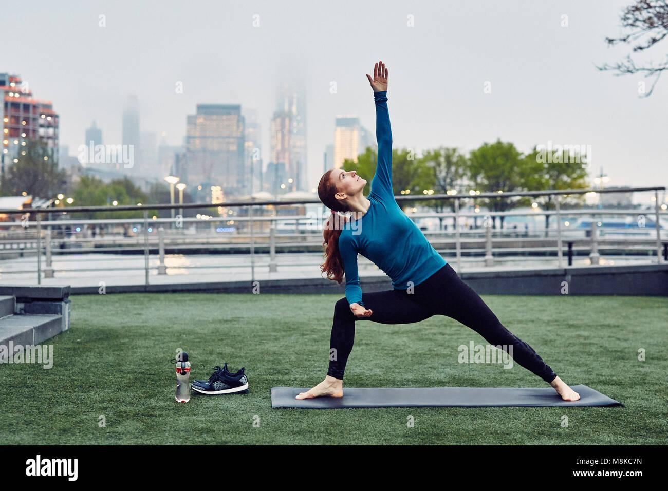 Caucasian Woman effectue le Yoga dans un parc public de la ville de New York Photo Stock