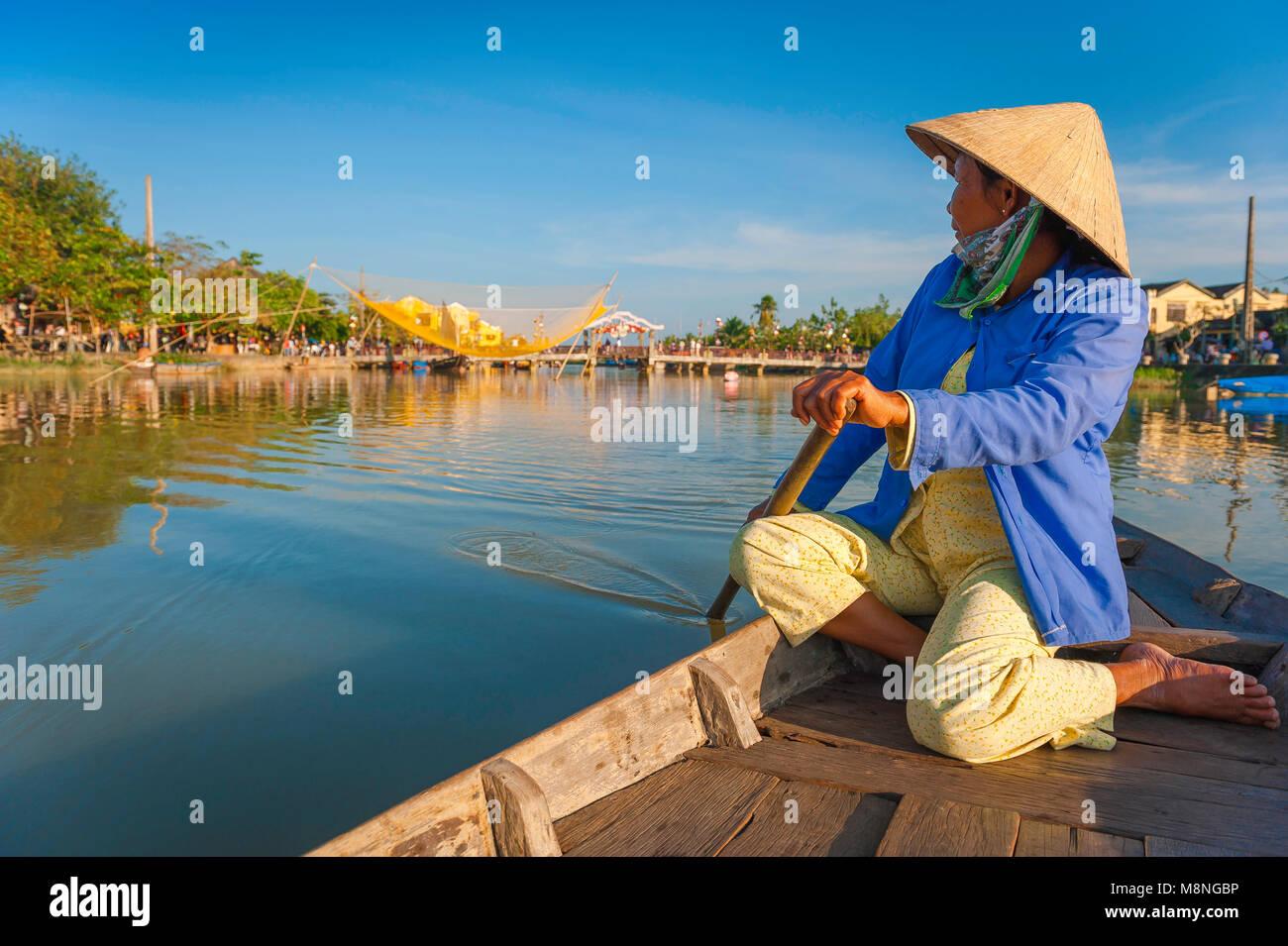 Hoi An river, un bateau-vietnamiens 'lady' dans un chapeau conique rangées le long de la rivière Photo Stock