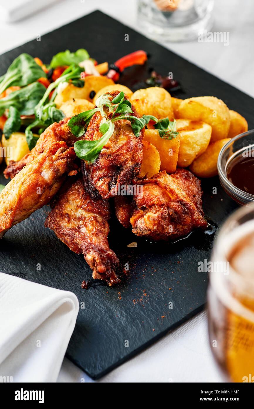 Ailes de poulet rôti avec des pommes de terre frites Photo Stock