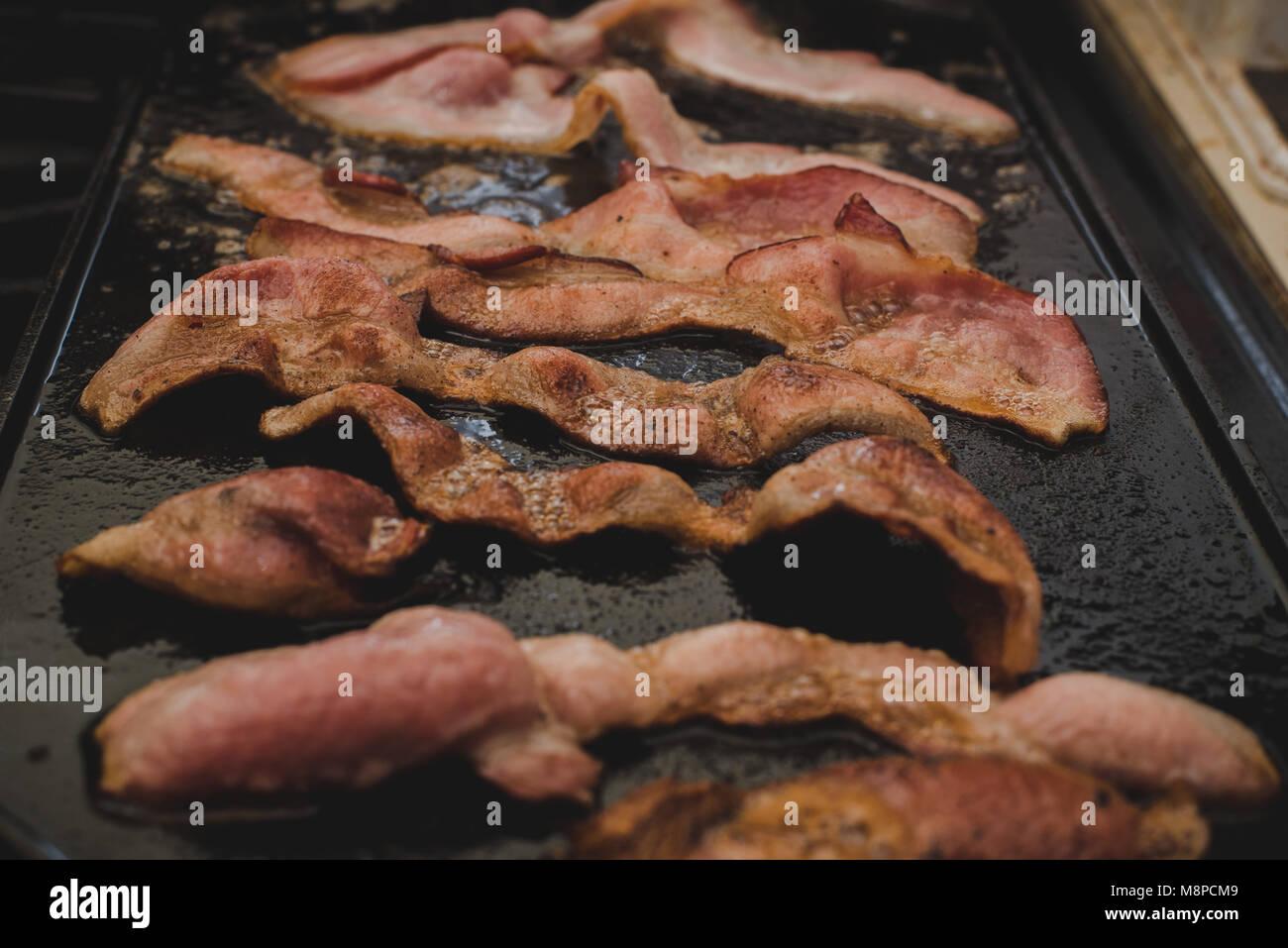 Un gros plan pour bacon sizzling sur une crêpière. Photo Stock