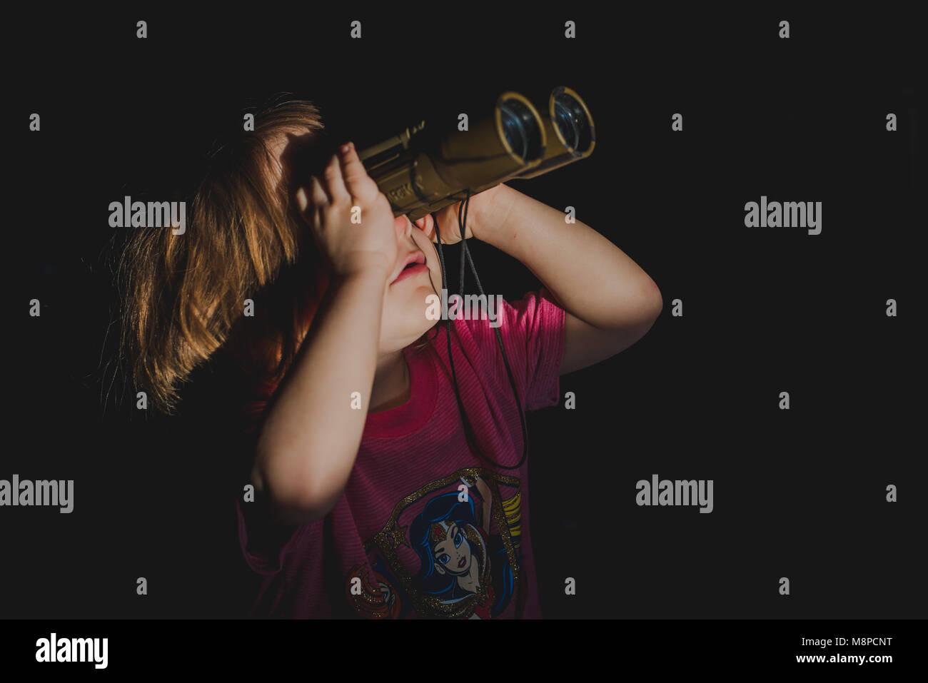 Un jeune bébé fille regardant à travers des jumelles. Photo Stock