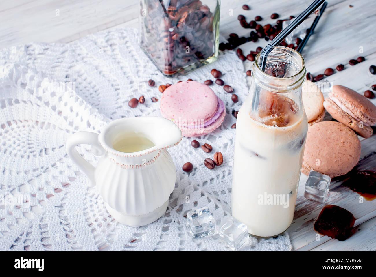 Glace café en verre, macarons,, morceaux de chocolat et les grains de café sur une table gris , vue d'en haut, copy space Banque D'Images