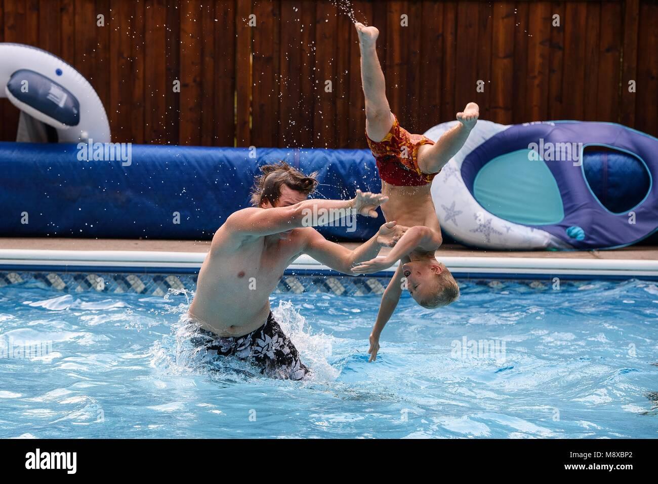 Deux garçons jouant dans la piscine un jour d'été Banque D'Images
