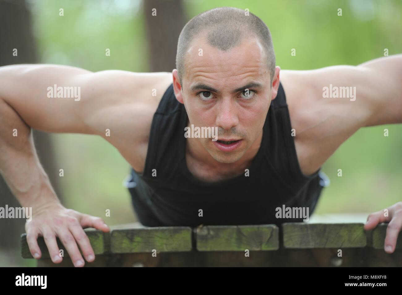 Jeune homme musclé faisant pushups Photo Stock