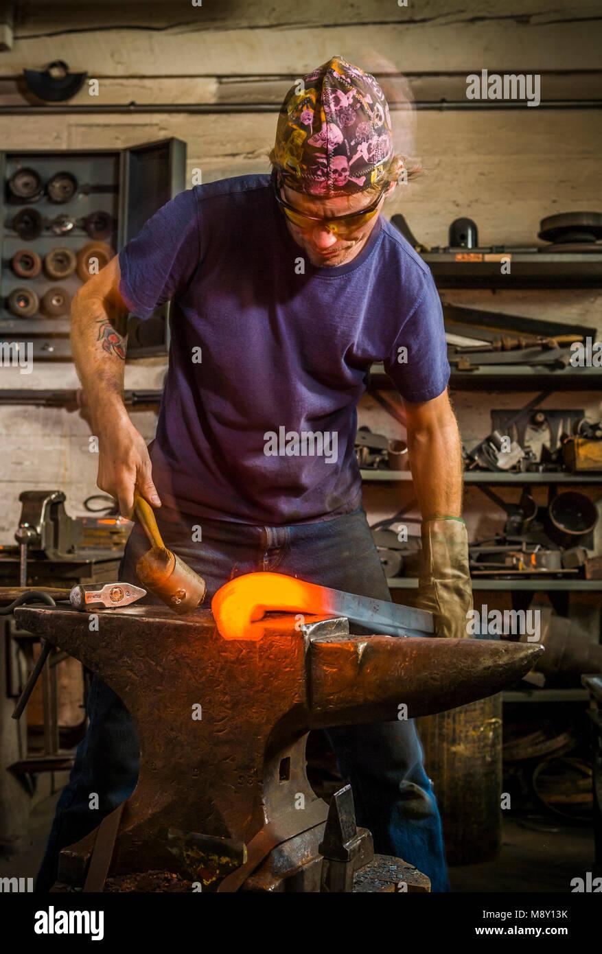 Un homme travaillant dans un atelier de forgeron avec marteau et enclume. Photo Stock