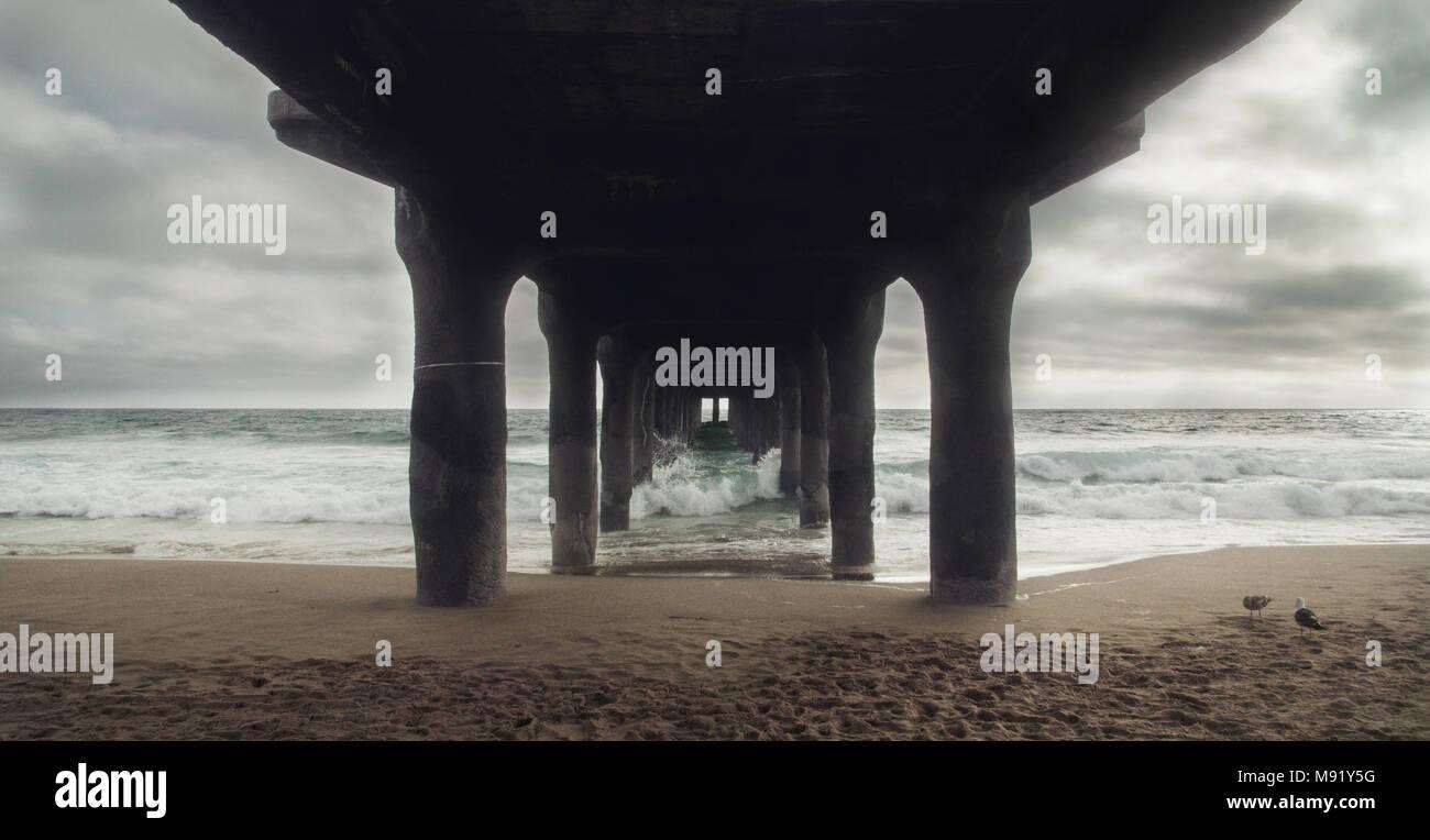 Un paysage morne prises sous la jetée, avec des vagues s'écraser sur ses jambes. Photo Stock
