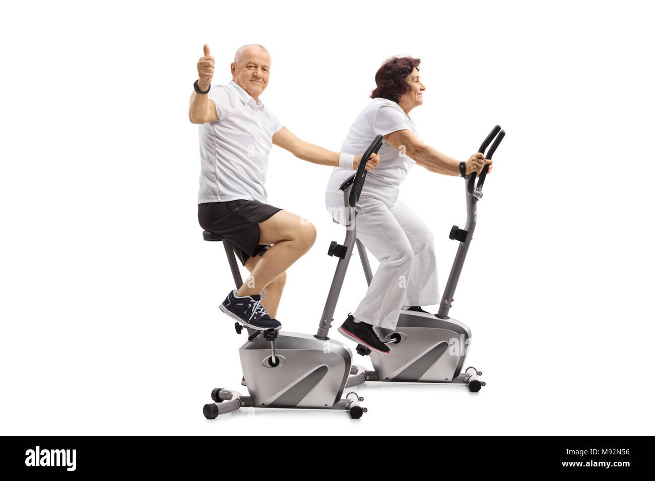 Homme mûr et d'une femme mature sur des vélos d'exercice avec l'homme de faire un pouce vers le haut signe isolé sur fond blanc