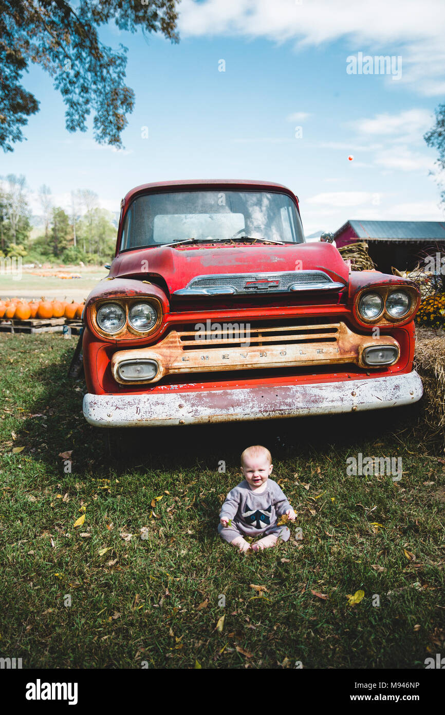 Baby sitting in front of red truck Photo Stock