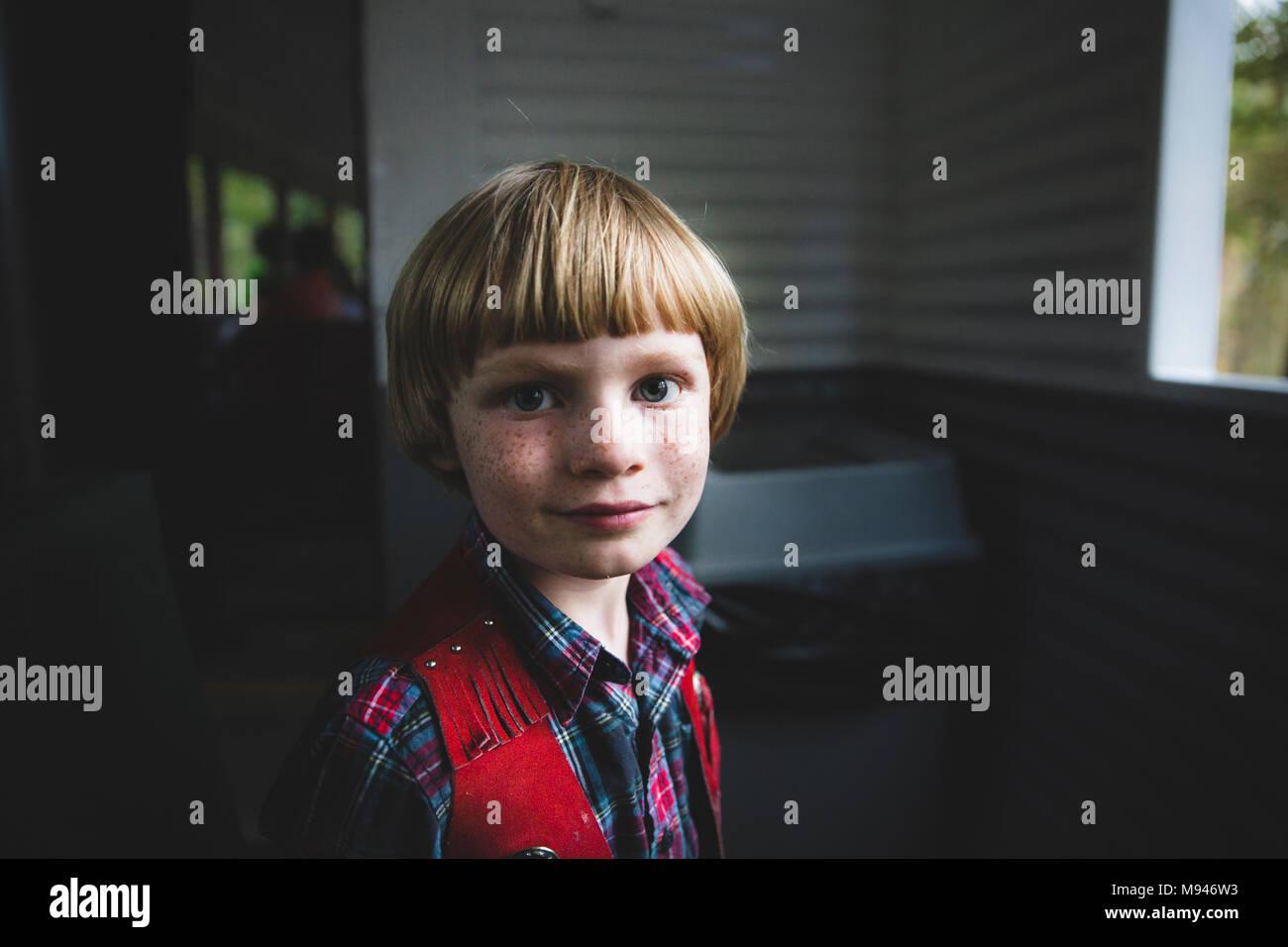 Garçon avec des taches de rousseur à la caméra en Photo Stock