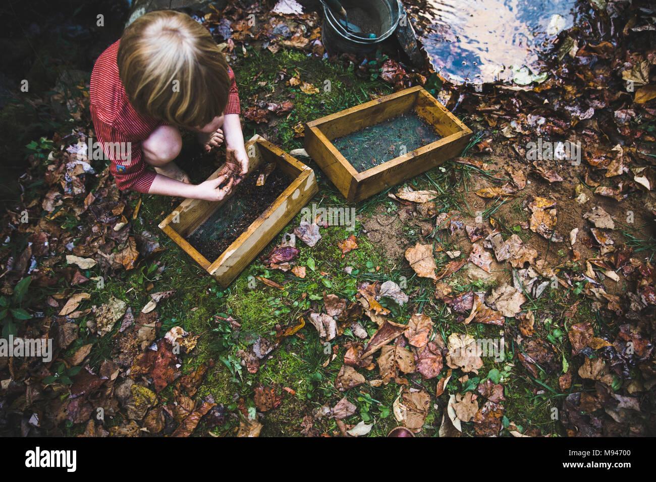 Les enfants en utilisant des seaux de panoramique à côté de river Photo Stock