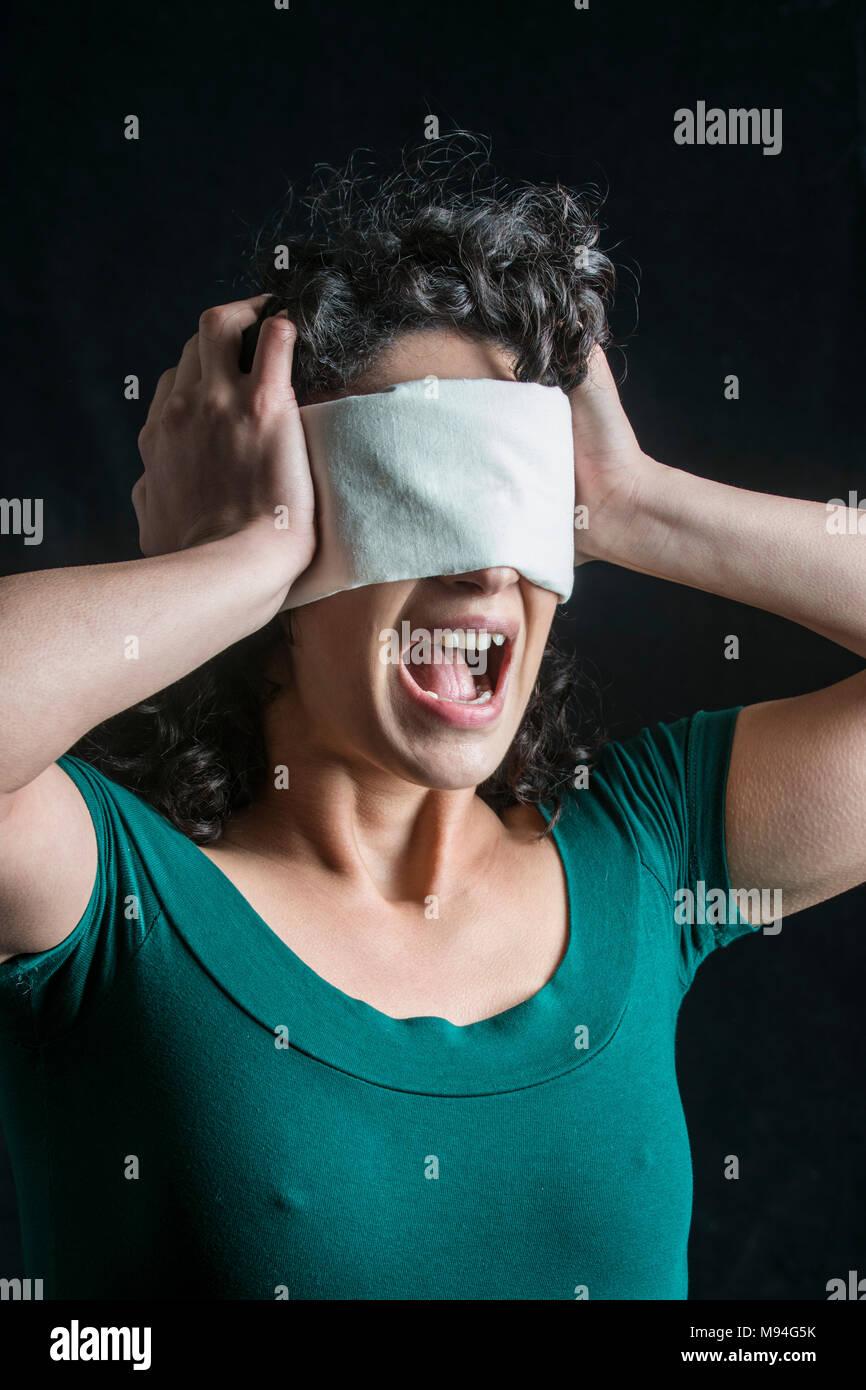 Portrait d'une femme aux cheveux noirs, les yeux bandés Photo Stock