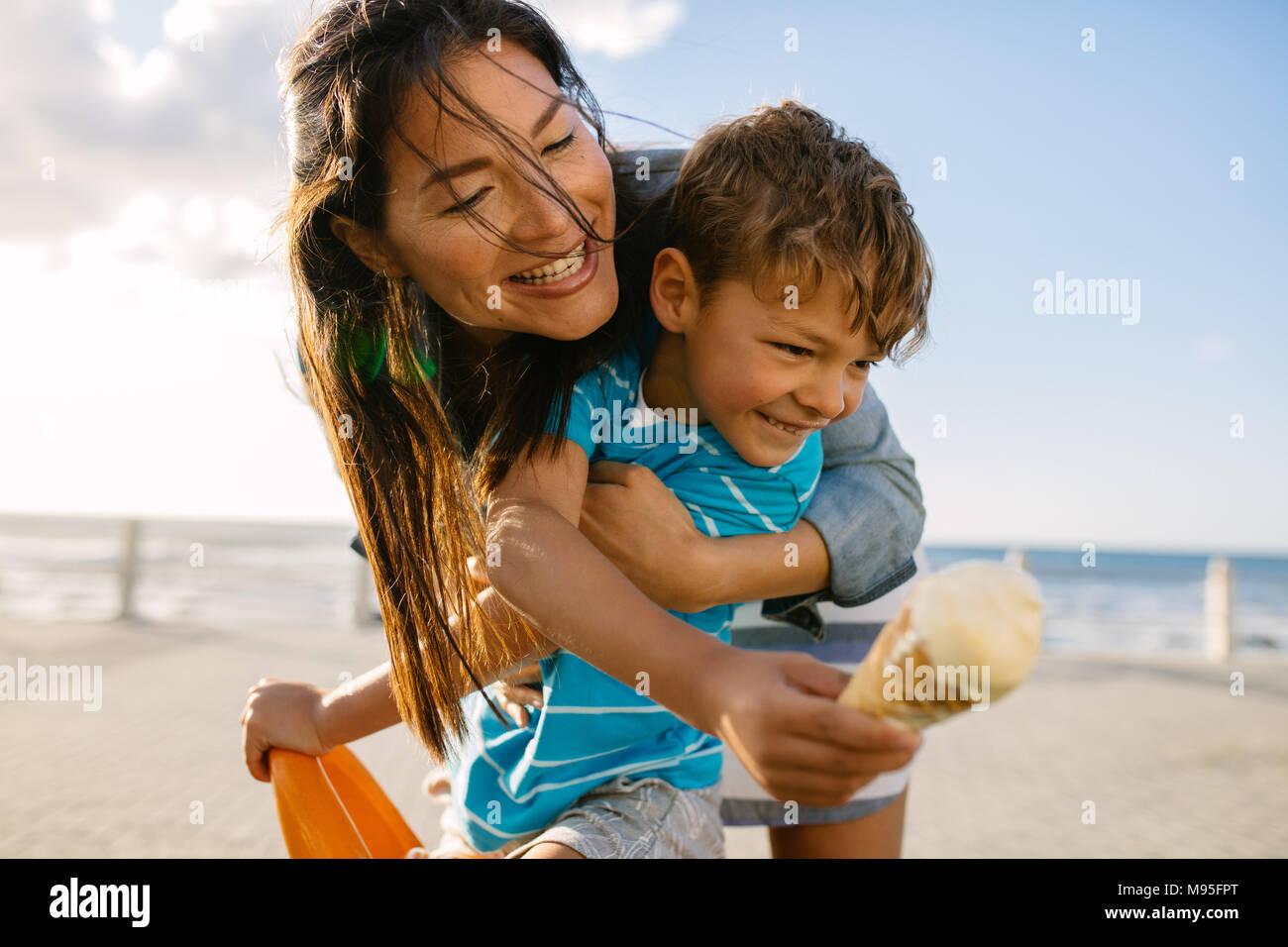 Garçon mangeant une glace près de front de mer avec sa mère. Petit garçon tenant un cornet de crème glacée pendant que sa mère s'efforce de le manger par derrière. Photo Stock