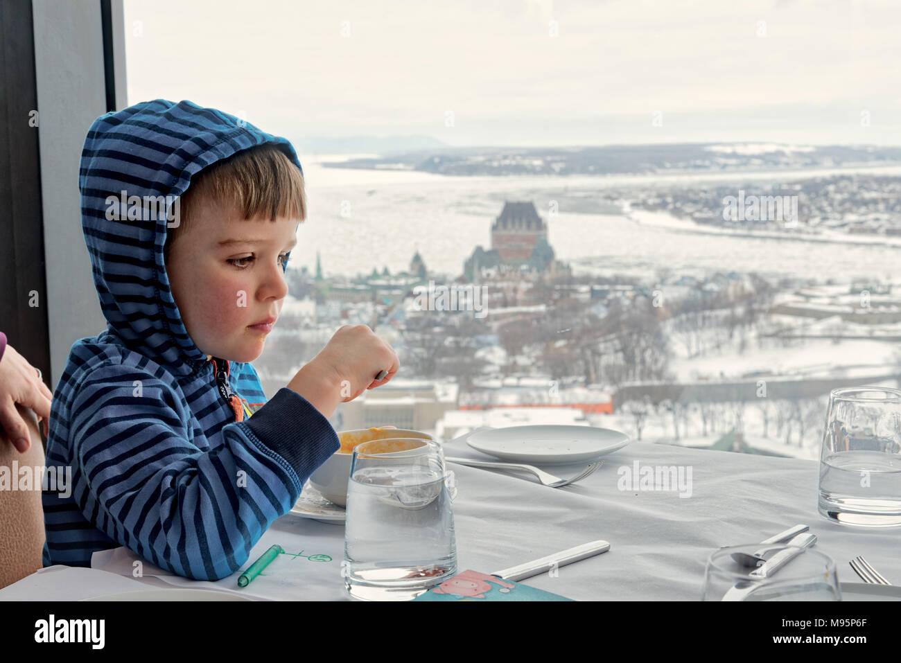 Un garçonnet de cinq ans manger dans le ciel! Restaurant dans la ville de Québec, avec le Château Frontenac et le fleuve Saint-Laurent gelé au-delà. Photo Stock
