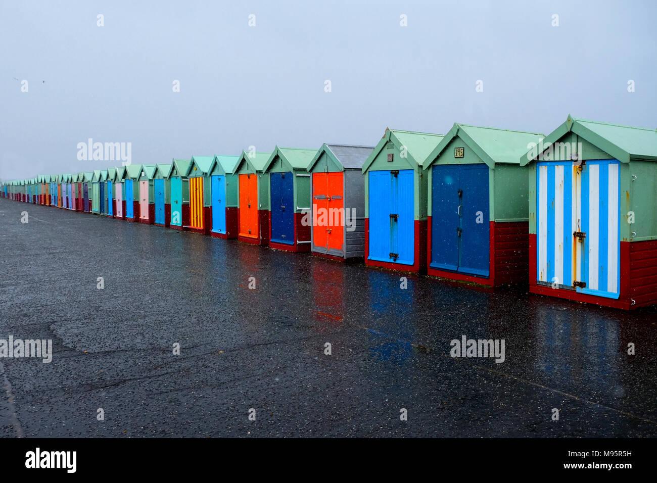 Une ligne de 40 cabanes de plage avec différentes portes multicolores sur une promenade de béton, le plus proche des cabines de plage sur la droite de l'image sont grandes va t Photo Stock