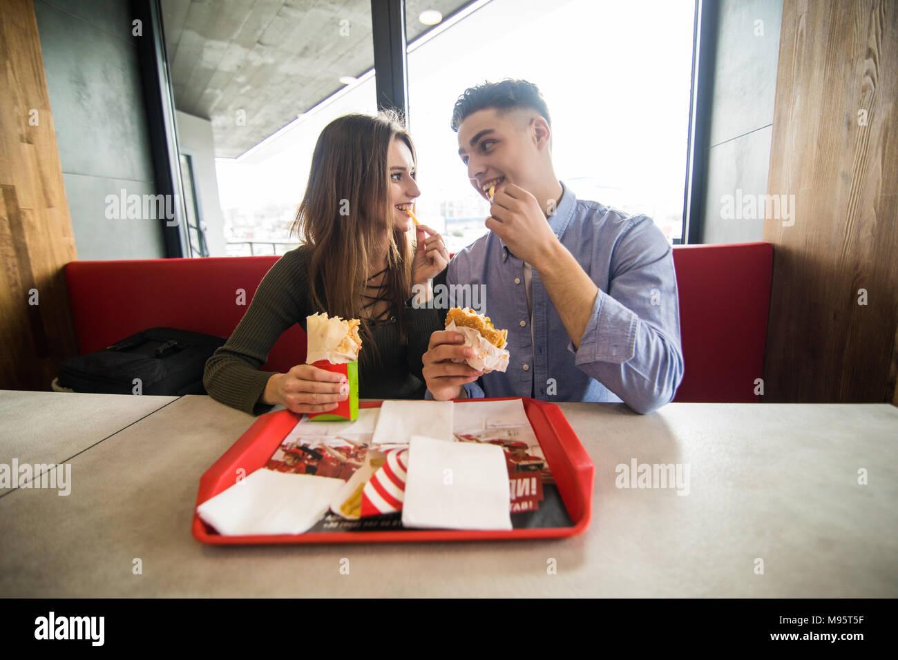 Heureux couple eating fast food burger et döner dans fast food cafe Photo Stock