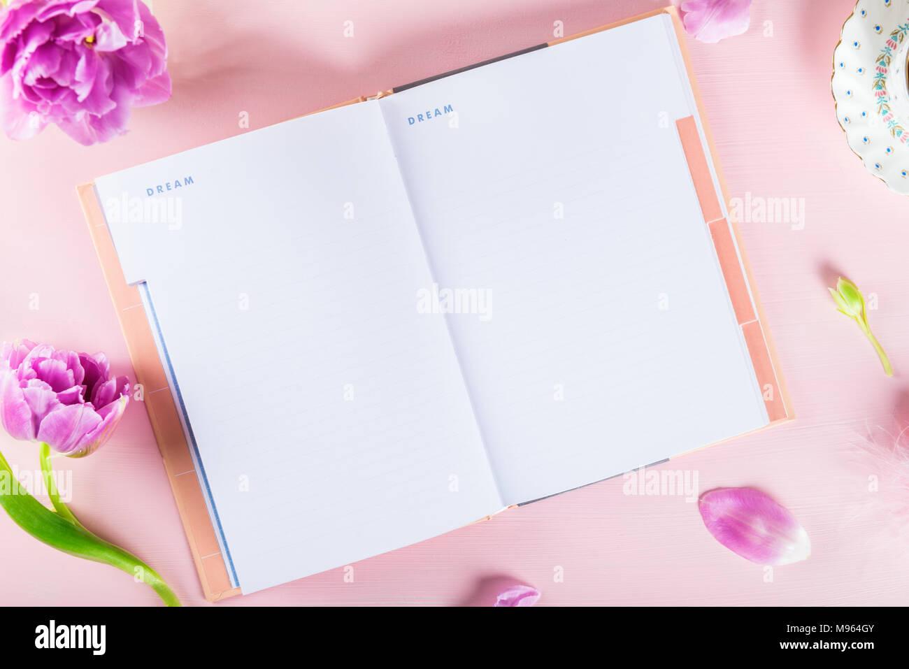 Ordinateur portable ouvert pour écrire les plans ou les rêves, girly paramètres sur la table avec bouquet de tulipes et de fond rose. Rêver grand concept Photo Stock