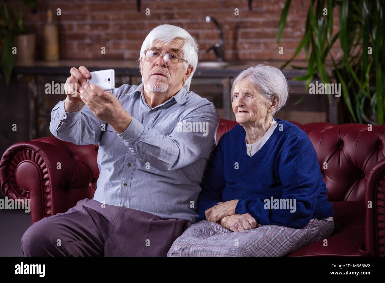 Young couple on smart phone selfies en étant assis sur la table à la maison Photo Stock