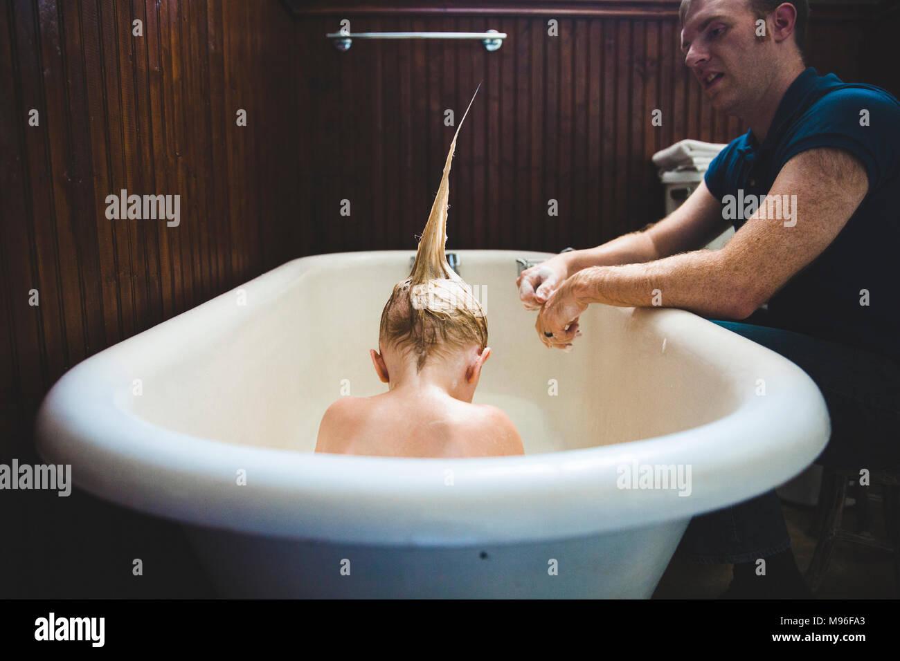 Père de l'enfant avec la coiffure hérissée de baignade Banque D'Images