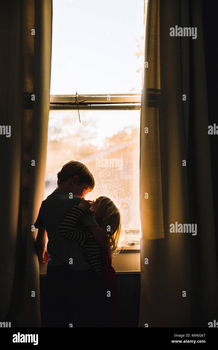 Serrant les enfants à côté de l'espace fenêtre dim Banque D'Images
