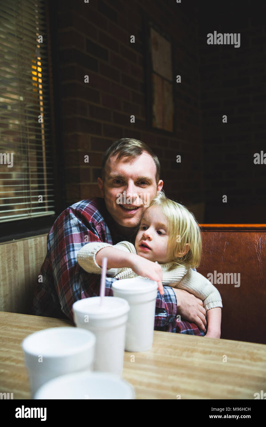 Man holding daughter in diner booth avec des verres en plastique sur la table Photo Stock