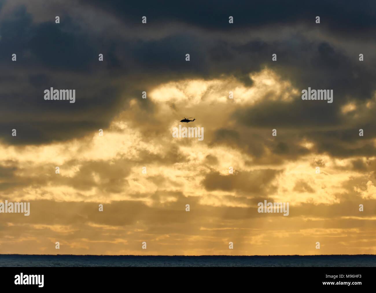 Un hélicoptère de revenir sous nuage noir, à la côte de la Norvège après avoir terminé les opérations de changement d'équipage sur un navire sismique en mer du Nord. Photo Stock