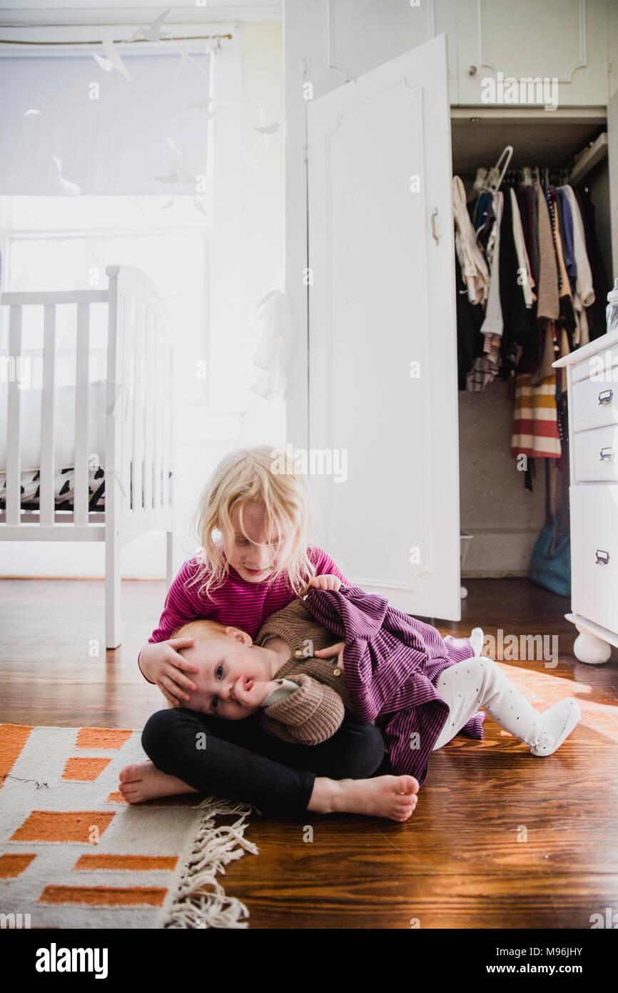 Girl avec bébé portant sur ses genoux Photo Stock