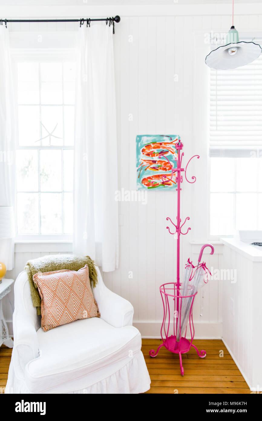 Chaise blanche à côté des crochets à vêtements rose en blanc accueil Photo Stock