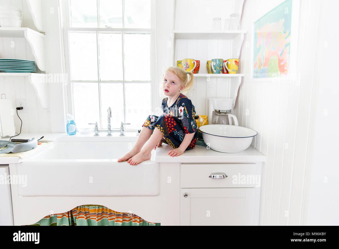 Girl par des yeux assis sur le plan de travail de cuisine Photo Stock