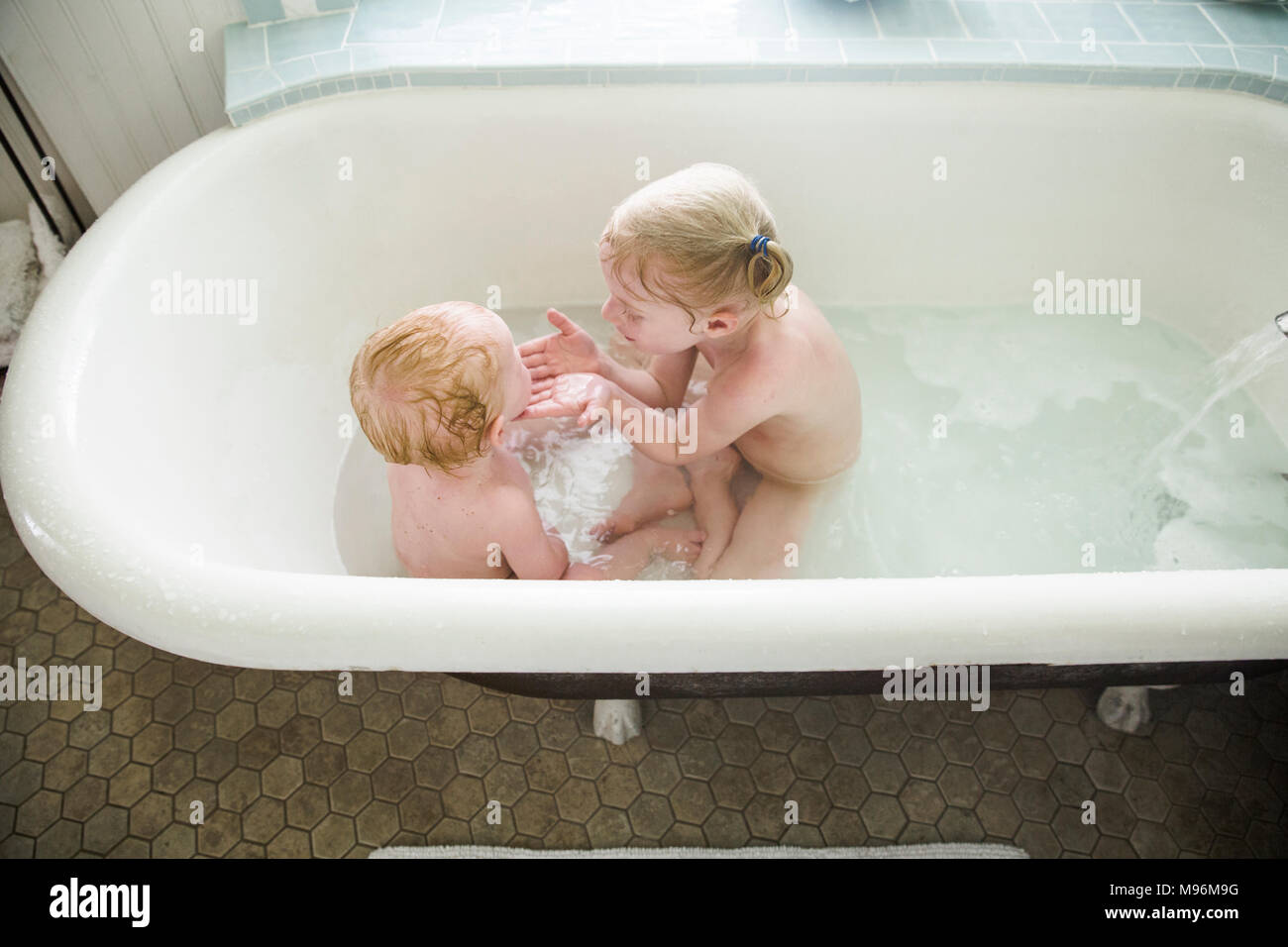 Girl washing baby sister à Bath Photo Stock