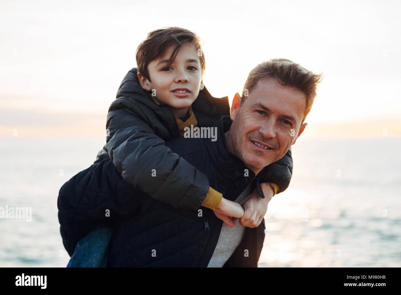Portrait of father carrying son piggyback sur la plage Photo Stock