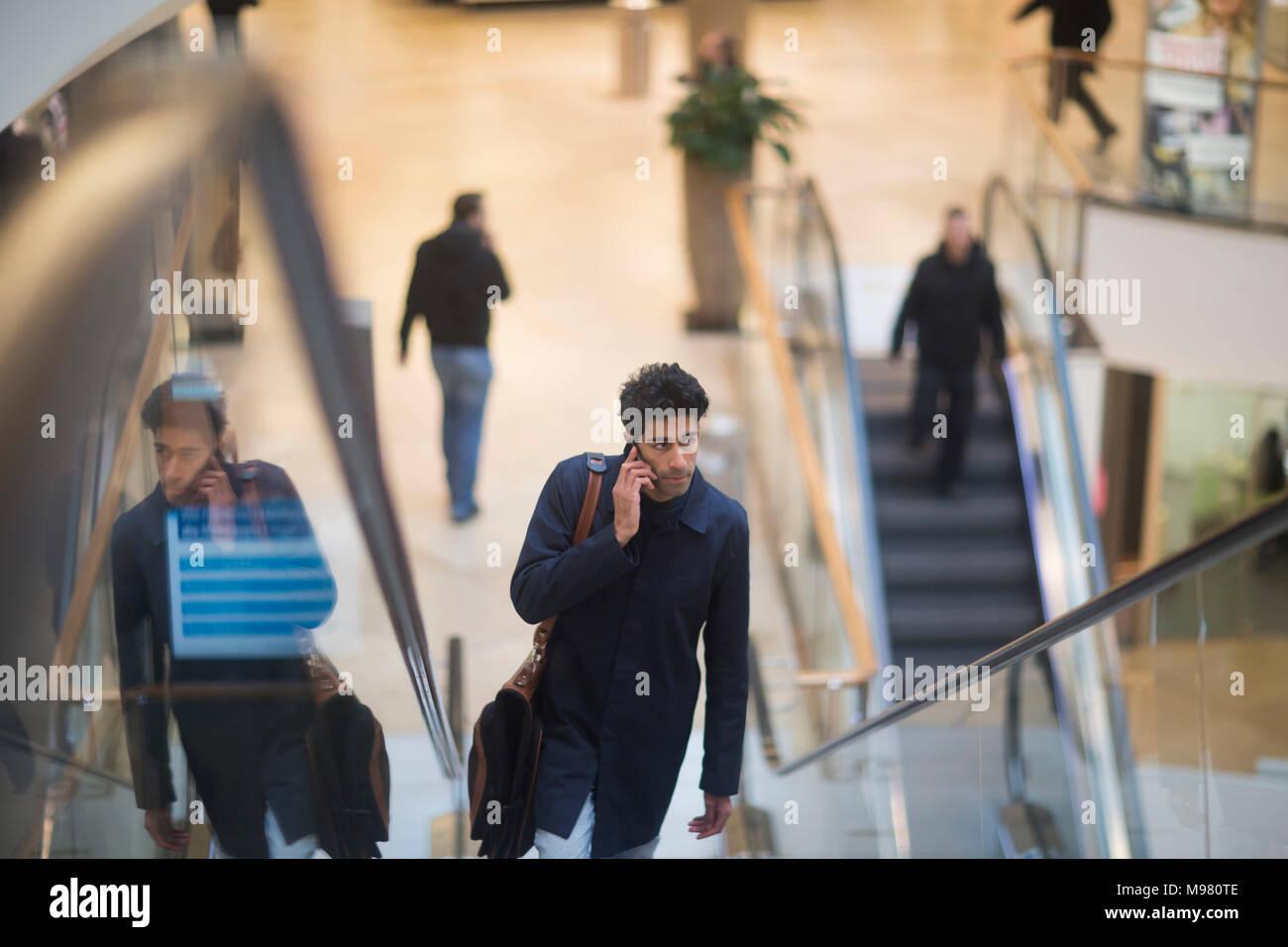 Homme au téléphone debout sur escalator dans un centre commercial Photo Stock
