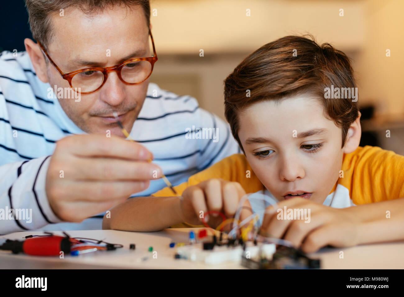 Le père et le fils de l'assemblage d'un kit de construction électronique Photo Stock