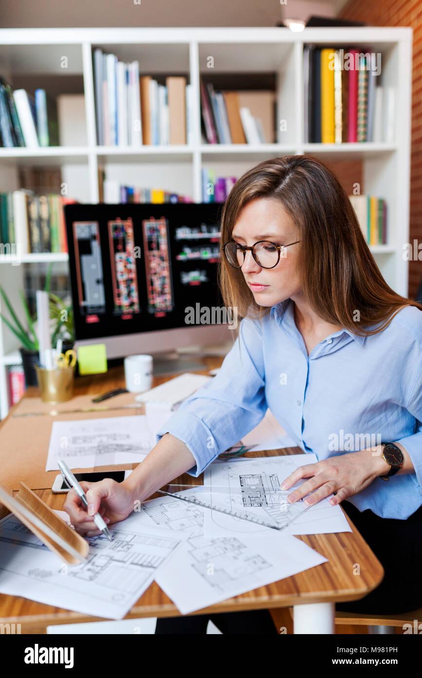 Jeune femme travaillant au bureau d'architecture Photo Stock