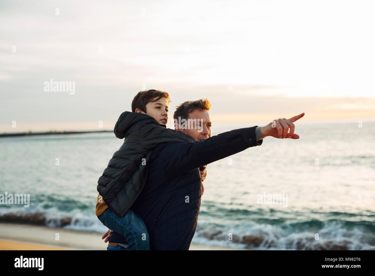 Father carrying son piggyback sur la plage au coucher du soleil montre de l'index Photo Stock