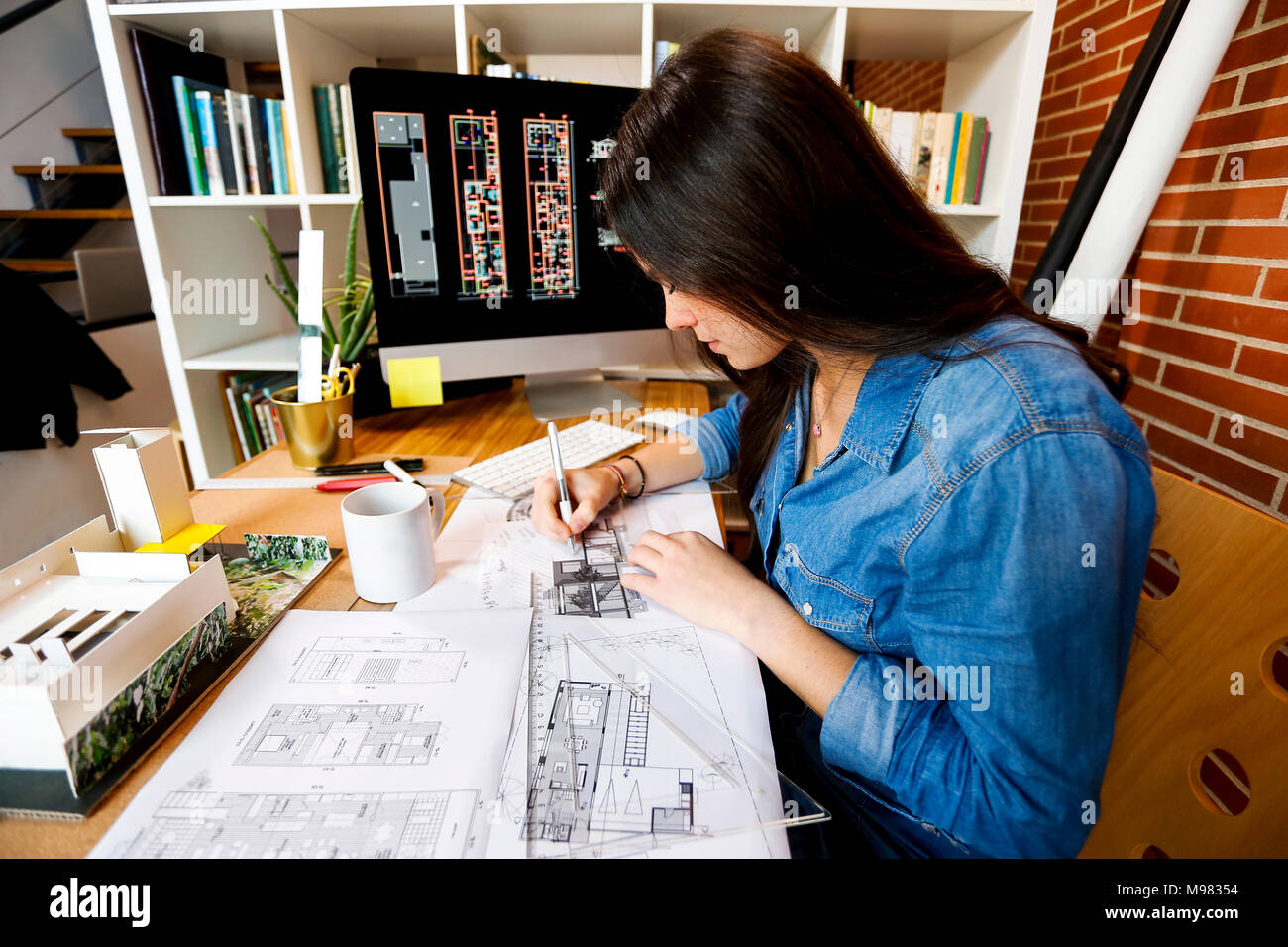 Jeune femme travaillant au bureau d'architecture, d'encombrement des bleus Photo Stock
