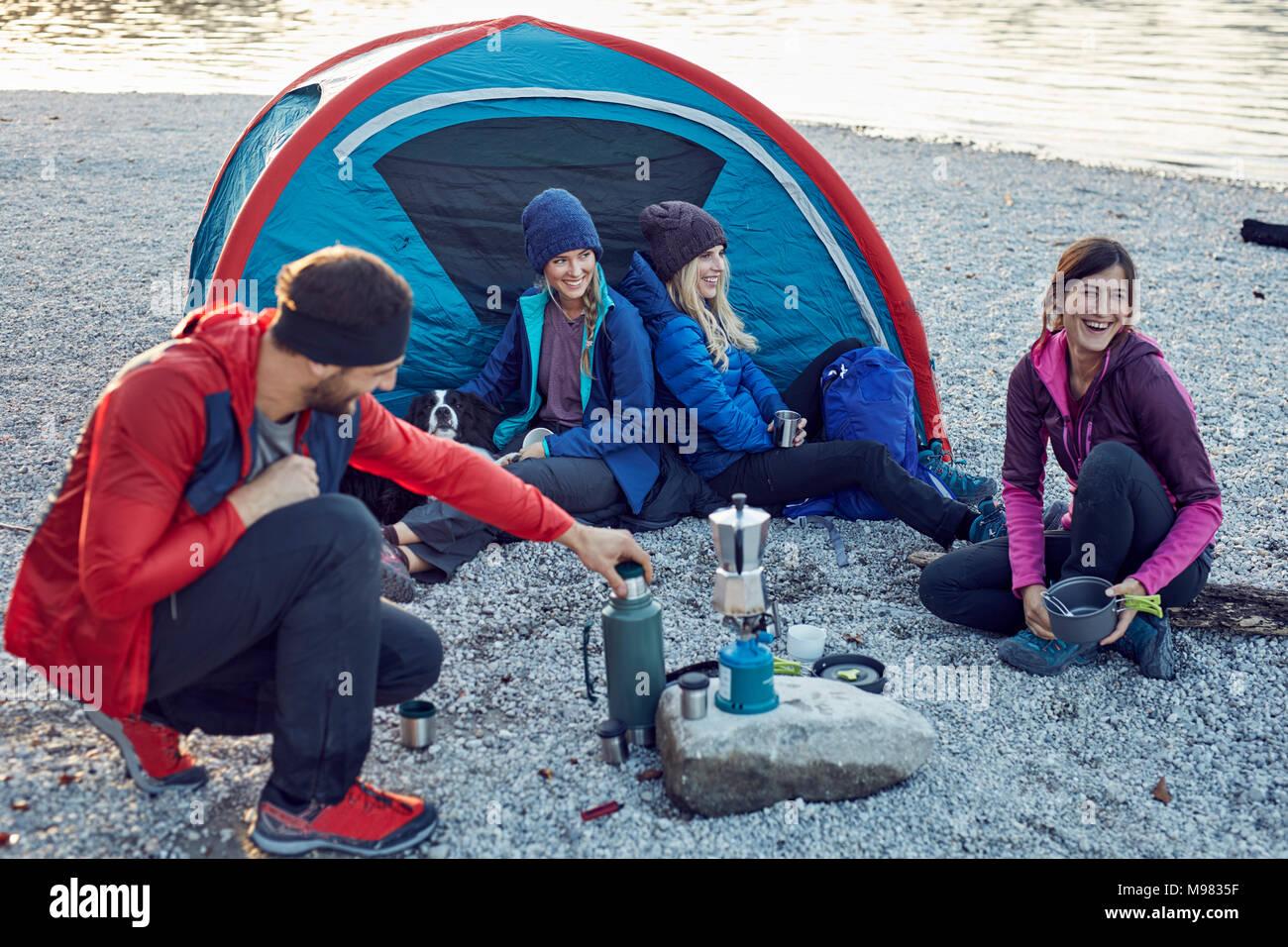 Groupe de randonneurs du camping au lac au coucher du soleil Photo Stock